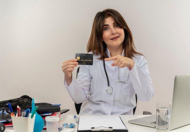 Impressed middle-aged female doctor wearing medical robe and stethoscope sitting at desk with medical tools clipboard and laptop holding and pointing at credit card isolated