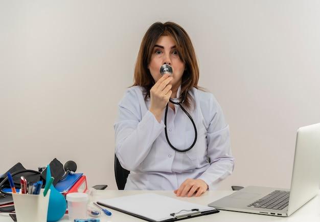 Medico femminile di mezza età impressionato che indossa veste medica e stetoscopio seduto alla scrivania con appunti di strumenti medici e laptop toccando le labbra con lo stetoscopio isolato