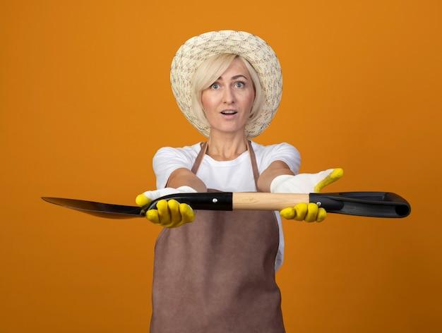 Впечатленная женщина-садовник средних лет в униформе садовника в шляпе и садовых перчатках протягивает лопату к камере, глядя вверх, изолированную на оранжевой стене