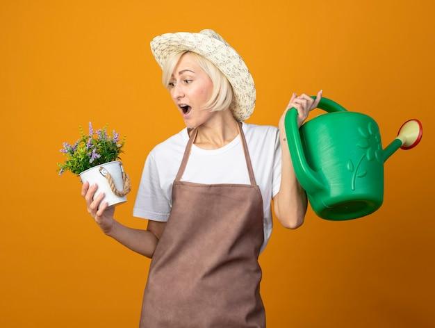 Впечатленная женщина-садовник средних лет в униформе садовника в шляпе держит лейку и цветочный горшок, глядя на горшок, изолированный на оранжевой стене