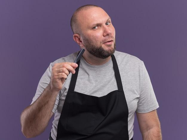 Впечатленный мужчина-парикмахер средних лет в униформе, держащий бритву, изолированную на фиолетовой стене