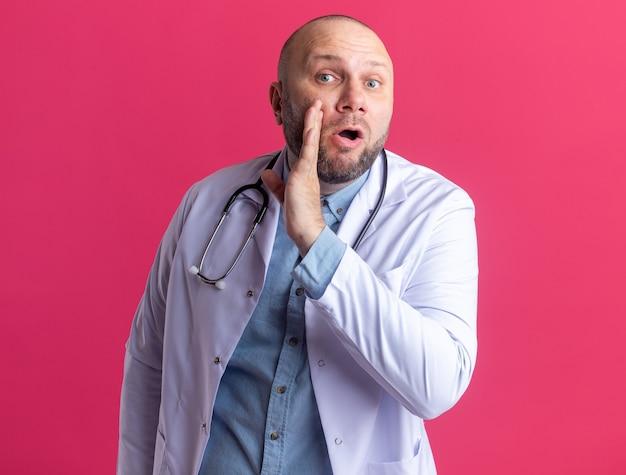 ピンクの壁に隔離された口の近くで手をささやきながら正面を見て医療ローブと聴診器を身に着けている印象的な中年男性医師
