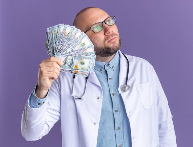 医療ローブと聴診器を身に着けている印象的な中年男性医師は、側面を見てお金を保持している眼鏡をかけています