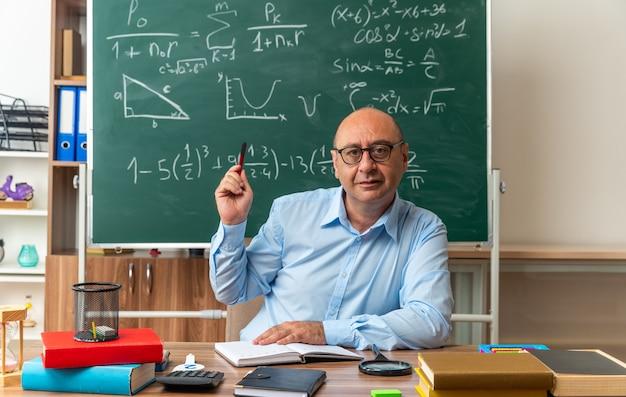眼鏡をかけている感動の中年男性教師は、教室でペンを保持している学用品とテーブルに座っています