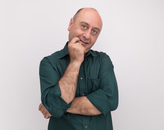 흰 벽에 고립 된 입에 손가락을 넣어 녹색 티셔츠를 입고 감동 중년 남자