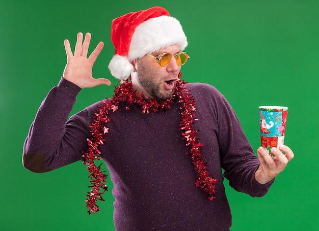Впечатленный мужчина средних лет в новогодней шапке и мишурной гирлянде на шее в очках, держащий и смотрящий на пластиковый рождественский стаканчик, поднимающий руку, изолированную на зеленой стене