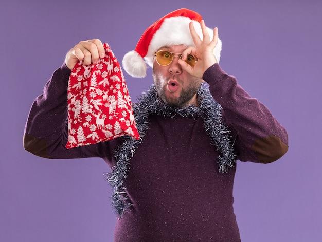 산타 모자와 크리스마스 선물 자루를 들고 안경 목 주위에 산타 모자와 반짝이 갈 랜드를 입고 감동하는 중년 남자가 보라색 배경에 고립 된 모습 제스처를하고 카메라를보고