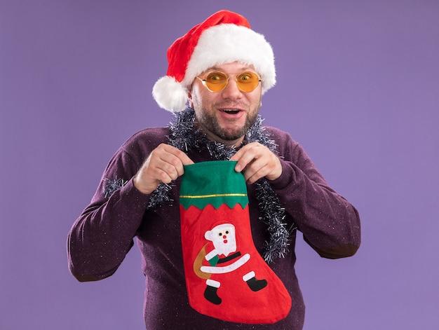 Впечатленный мужчина средних лет в шляпе санта-клауса и гирлянде из мишуры на шее в очках, держащий рождественский чулок, изолированный на фиолетовой стене