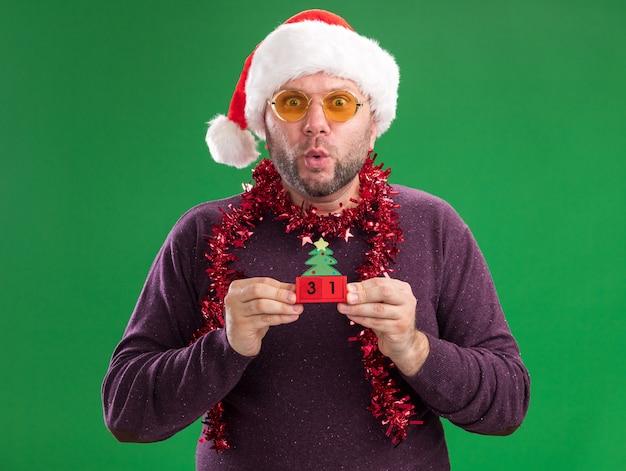 緑の背景に分離された口すぼめ呼吸でカメラを見て日付とクリスマスツリーのおもちゃを保持しているメガネと首の周りにサンタの帽子と見掛け倒しの花輪を身に着けている印象的な中年男性