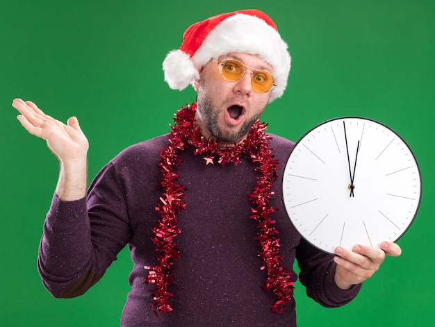 Впечатленный мужчина средних лет в шляпе санта-клауса и гирлянде из мишуры на шее в очках с часами, показывающими пустую руку, изолированную на зеленой стене