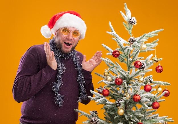 Впечатленный мужчина средних лет в новогодней шапке и мишурной гирлянде на шее в очках, стоящий возле украшенной елки