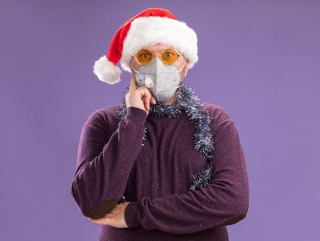 Impressionato uomo di mezza età che indossa cappello da babbo natale e maschera protettiva con ghirlanda di orpelli intorno al collo con gli occhiali tenendo la mano sul mento isolato sul muro viola