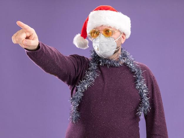 Impressionato uomo di mezza età che indossa cappello da babbo natale e maschera protettiva con ghirlanda di orpelli intorno al collo con gli occhiali che guardano e indicano il lato isolato sul muro viola