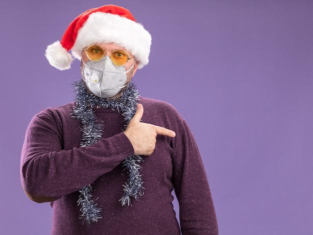 Impressionato uomo di mezza età che indossa cappello da babbo natale e maschera protettiva con ghirlanda di orpelli intorno al collo con occhiali rivolti sul lato isolato sul muro viola con spazio di copia