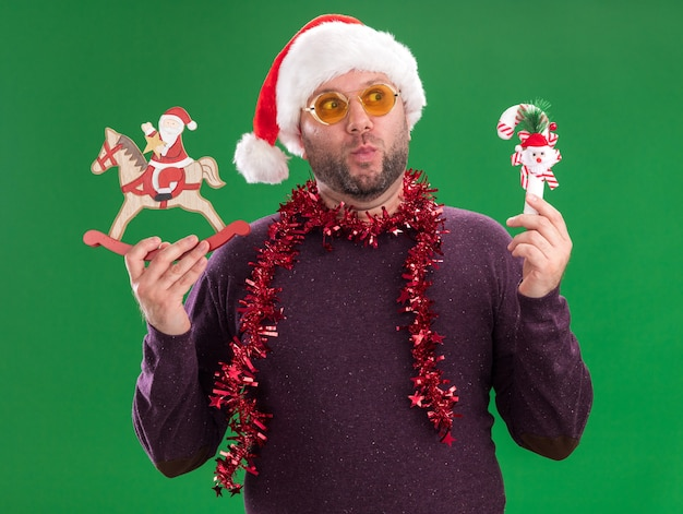 Impressed middle-aged man wearing santa hat and tinsel garland around neck with glasses holding candy cane ornament and santa