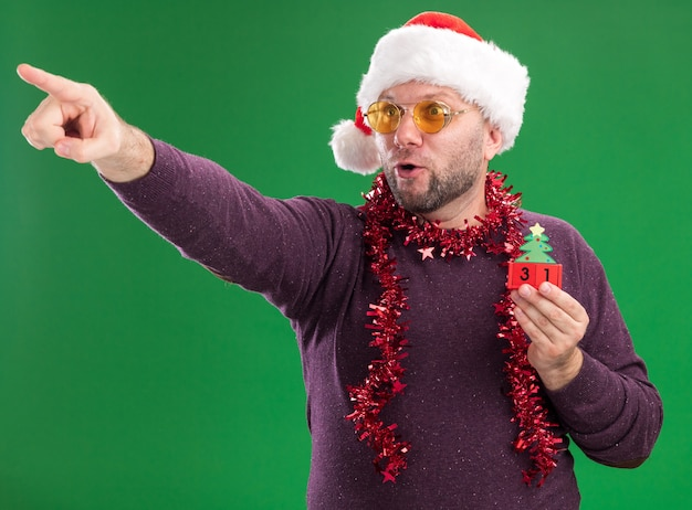 Impressed middle-aged man wearing santa hat and tinsel garland around neck with glasses holding christmas tree toy with date looking and pointing at side isolated on green wall