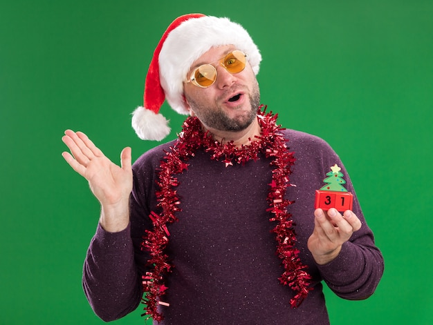 Impressed middle-aged man wearing santa hat and tinsel garland around neck with glasses holding christmas tree toy with date