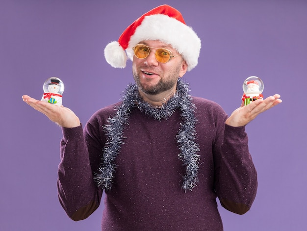Impressionato uomo di mezza età che indossa il cappello di babbo natale e la ghirlanda di orpelli intorno al collo con gli occhiali che tengono le figurine del pupazzo di neve e di babbo natale isolate sul muro viola