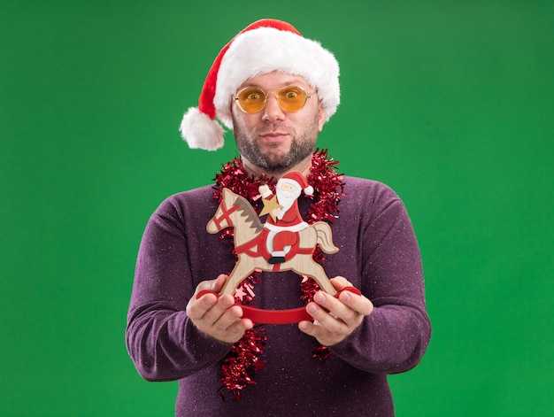Impressed middle-aged man wearing santa hat and tinsel garland around neck with glasses stretching out santa on rocking horse figurine   isolated on green wall
