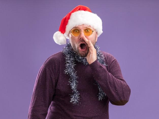 Uomo di mezza età impressionato che indossa un cappello da babbo natale e una ghirlanda di orpelli intorno al collo con gli occhiali che bisbigliano isolato sul muro viola