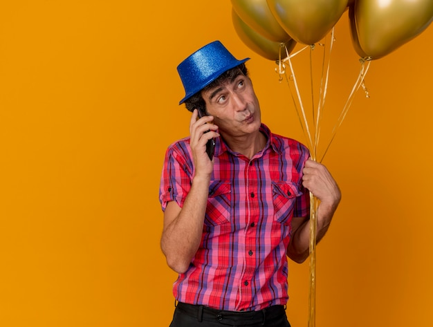 Impressed middle-aged party man wearing party hat holding balloons talking on phone looking at side isolated on orange wall