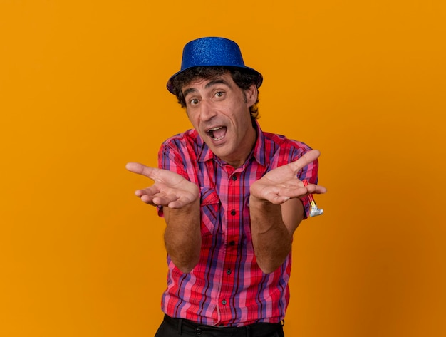 복사 공간 오렌지 벽에 고립 된 빈 손을 보여주는 전면을보고 파티 모자를 쓰고 감동 된 중년 파티 남자