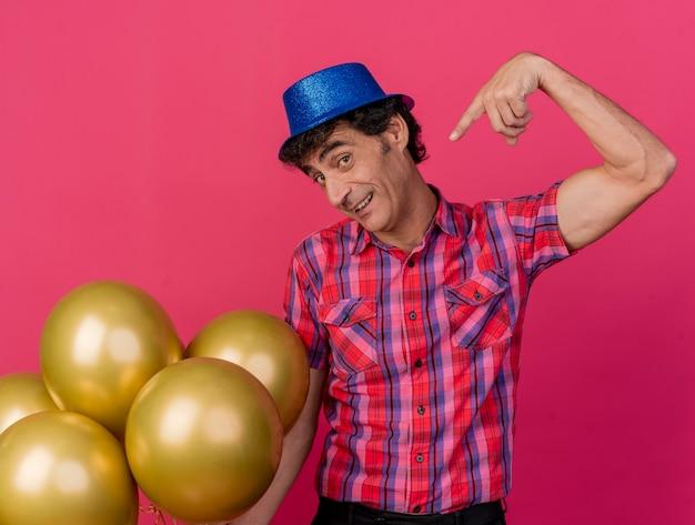 Impressionato uomo di mezza età che indossa un cappello da festa guardando davanti tenendo e indicando palloncini isolati sul muro cremisi