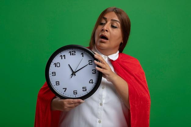 Impressionato supereroe femminile di mezza età che tiene e guardando l'orologio da parete isolato sul verde