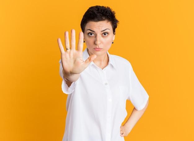 Впечатленная женщина средних лет, держащая руку на талии, глядя в камеру, делает стоп-жест
