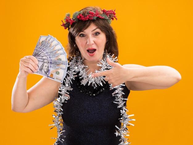 オレンジ色の背景に分離されたカメラを見てお金を保持し、指さし、首の周りにクリスマスのヘッドリースと見掛け倒しの花輪を身に着けている印象的な中年女性