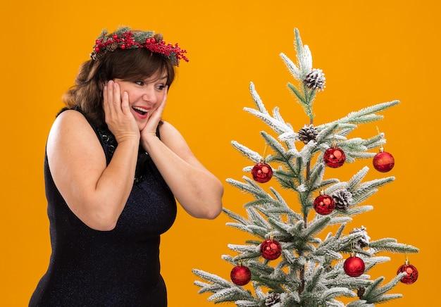 装飾されたクリスマスツリーの近くの縦断ビューで立っている首の周りにクリスマスのヘッドリースと見掛け倒しのガーランドを身に着けている感動の中年女性