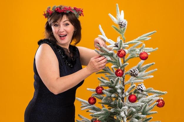 크리스마스 트리 근처에 서있는 목 주위에 크리스마스 머리 화환과 반짝이 갈 랜드를 입고 감동 중년 여성