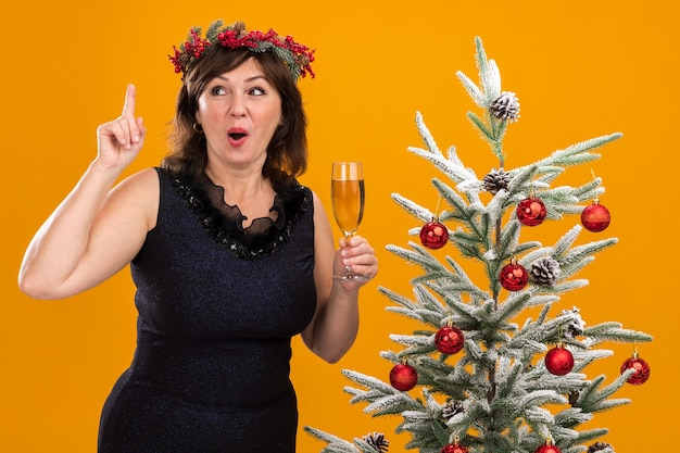 Impressionato donna di mezza età che indossa la testa di natale ghirlanda e tinsel ghirlanda intorno al collo in piedi vicino all'albero di natale decorato tenendo un bicchiere di champagne