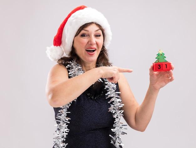 首の周りにサンタの帽子と見掛け倒しの花輪を身に着けている印象的な中年の女性は、白い背景で隔離のカメラを見て日付とクリスマスツリーのおもちゃを保持し、指しています