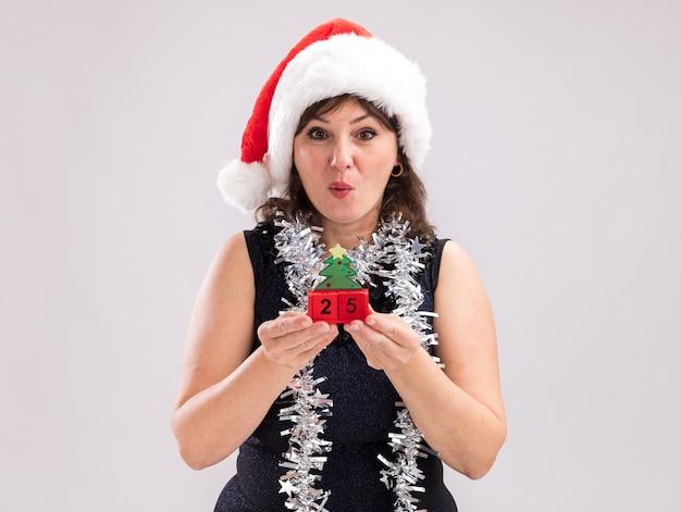 복사 공간 흰색 배경에 고립 된 카메라를보고 날짜와 크리스마스 트리 장난감을 들고 목 주위에 산타 모자와 반짝이 갈 랜드를 입고 감동 중년 여성