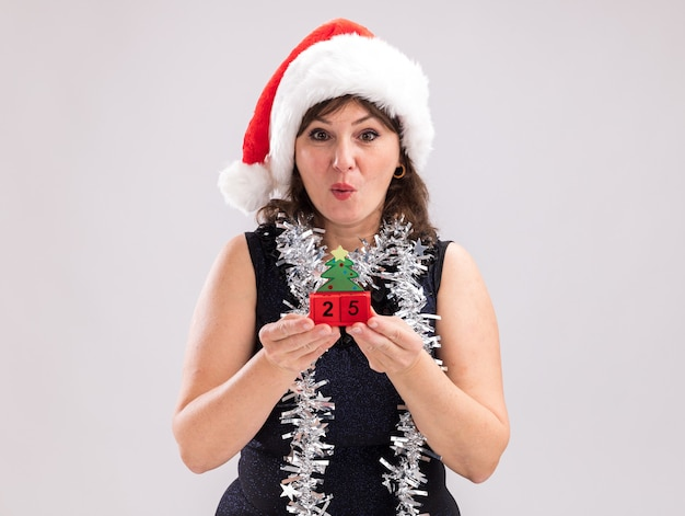 Impressed middle-aged woman wearing santa hat and tinsel garland around neck holding christmas tree toy with date looking at camera isolated on white background with copy space