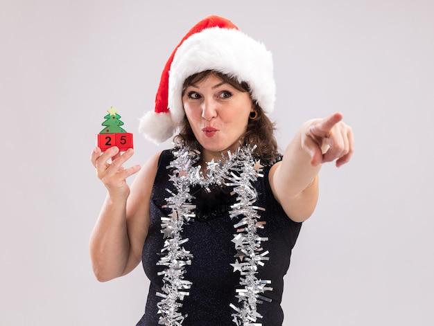 Donna di mezza età impressionata che indossa cappello da babbo natale e ghirlanda di orpelli intorno al collo che tiene il giocattolo dell'albero di natale con la data che guarda e indica il lato isolato su sfondo bianco