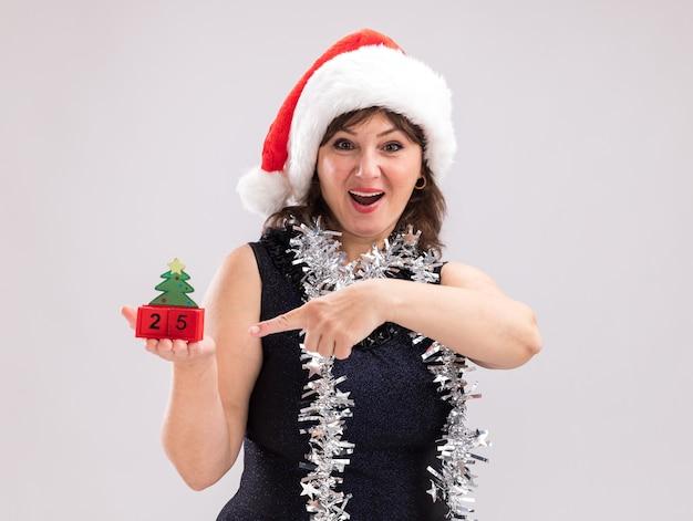 Impressionato donna di mezza età che indossa cappello da babbo natale e ghirlanda di orpelli intorno al collo tenendo e indicando il giocattolo dell'albero di natale con la data che guarda l'obbiettivo isolato su sfondo bianco