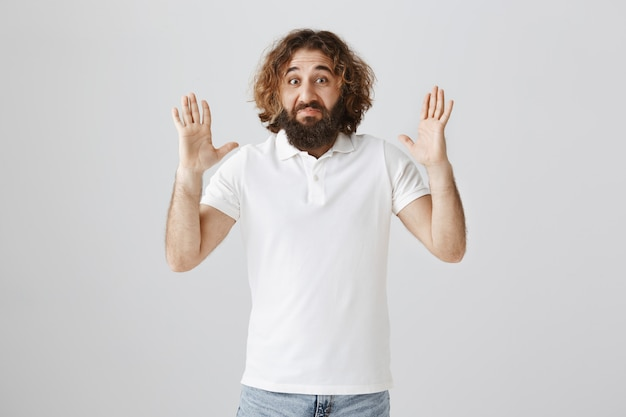 Impressed middle-eastern man with beard showing big object with stretched hands