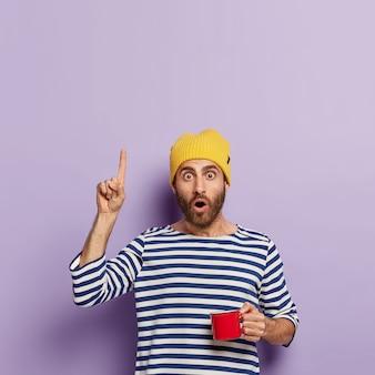 Il ragazzo millenario colpito punta verso l'alto con il dito indice, ha un'espressione scioccata, beve caffè al mattino, tiene una tazza rossa, indossa un cappello giallo e un maglione da marinaio a strisce, mostra qualcosa