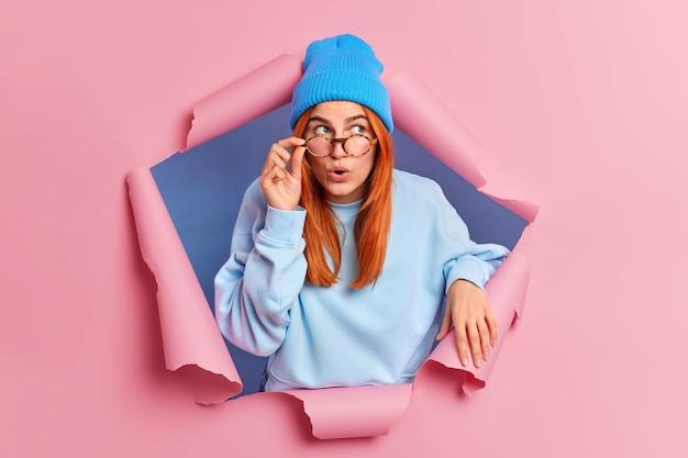 La donna millenaria impressionata guarda sorprendentemente sopra tiene la mano sugli occhiali indossa un maglione blu e il cappello sente notizie scioccanti.