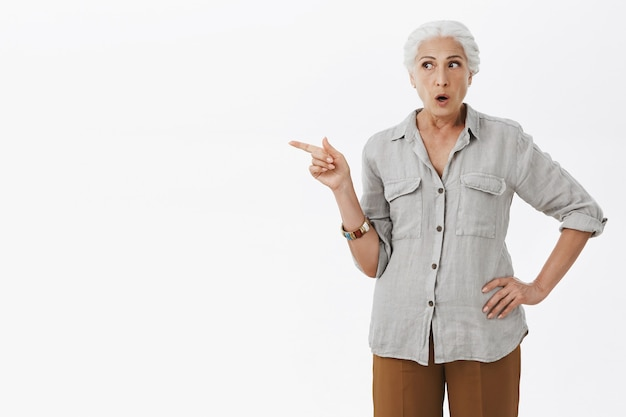 Impressed old woman pointing finger left, asking question about product
