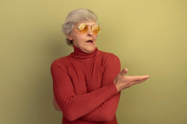 赤いタートルネックのセーターとサングラスを身に着けている印象的な老婆は、コピースペースのあるオリーブグリーンの壁に隔離された側を手で見て指しています