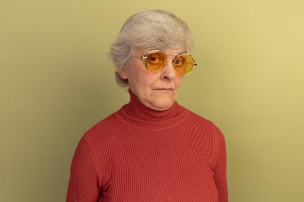 Una donna anziana impressionata che indossa un maglione a collo alto rosso e occhiali da sole guardando la parte anteriore isolata su una parete verde oliva con spazio per le copie