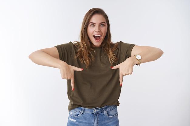 カジュアルな服装のドロップジョーを身に着けている印象的な圧倒的な魅力的な思春期の25代の女性は、驚いた人差し指を下に向けて面白がって、信じられないほどの販売広告コピースペースを示しています