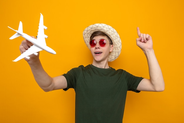 Impressed points at up young handsome guy wearing hat with glasses holding toy airplane