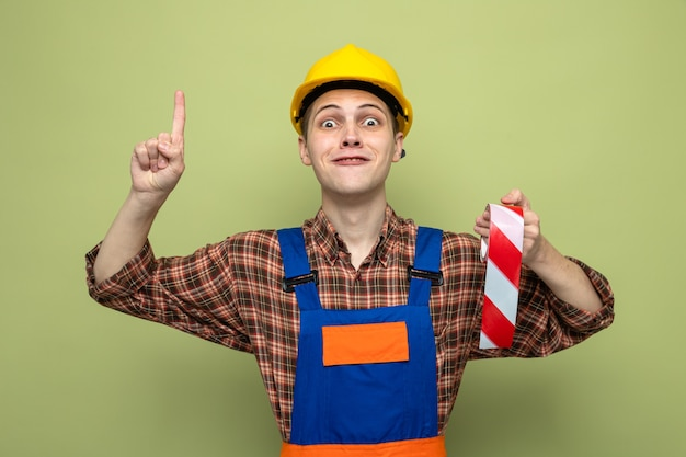 Impressed points at up young male builder wearing uniform holding duct tape
