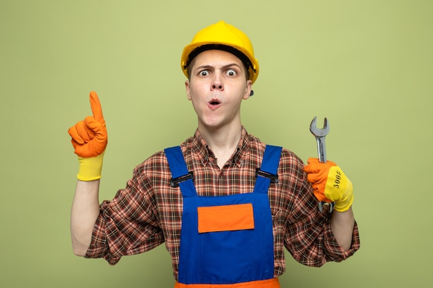 Punti impressionati su un giovane costruttore maschio che indossa un'uniforme con guanti che tengono una chiave aperta