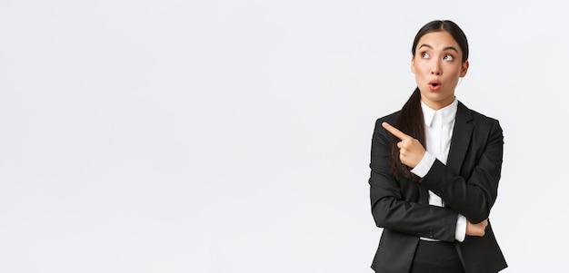 Впечатленная симпатичная азиатская женщина-менеджер, бизнесвумен в костюме, указывая и глядя в левый верхний угол с изумленным выражением лица, замечает хорошую сделку, стоя на белом фоне