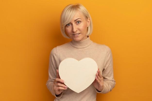 La donna slava abbastanza bionda impressionata tiene la forma del cuore isolata sulla parete arancione